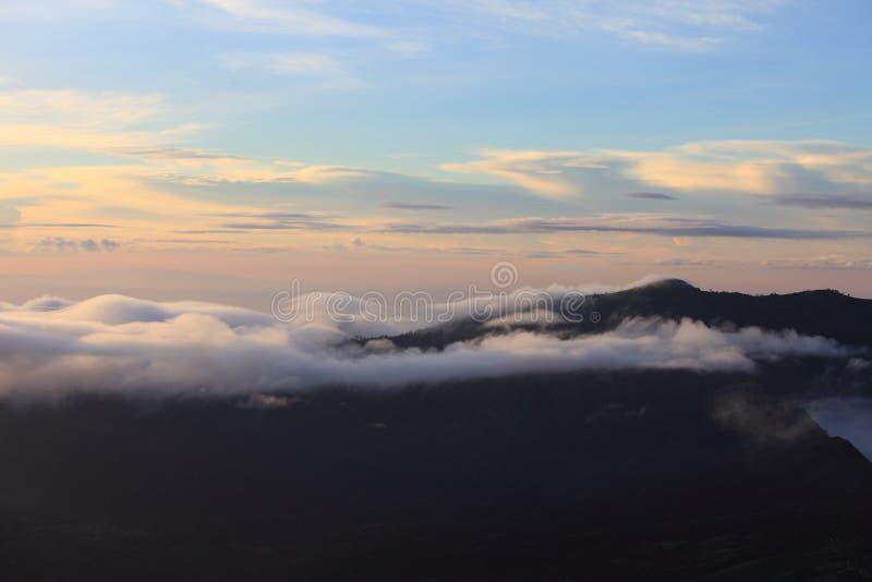 Ландшафт горы на заходе солнца Изумительный взгляд от горного пика на высоких облаках голубого неба утесов и моря в вечере облака стоковое изображение rf