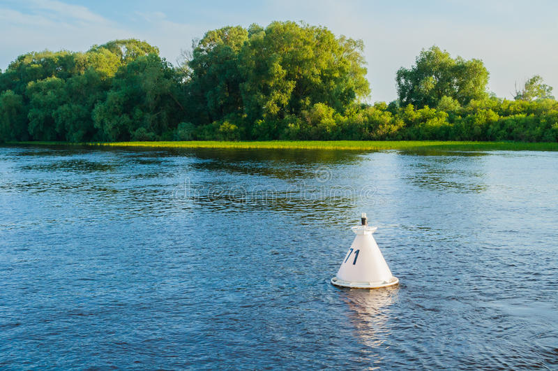 Ландшафт захода солнца воды лета - деревья вдоль банка реки и томбуя на воде под теплым заходом солнца освещают стоковая фотография rf