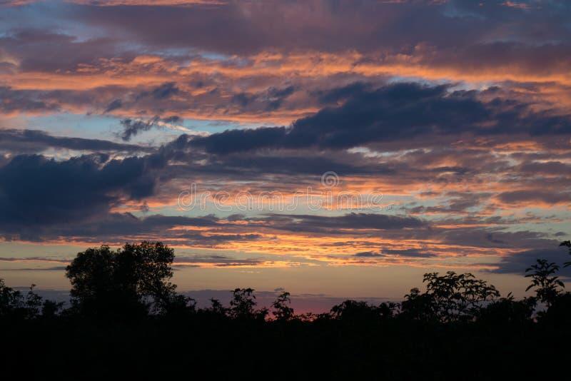 Ландшафт захода солнца с горящим небом полным облаков стоковая фотография rf