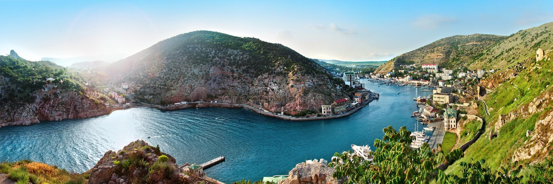 Ландшафт залива моря с горами голубого неба и зеленой травой стоковая фотография
