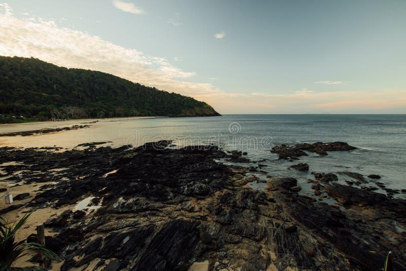 Ландшафт красивое море и скалистый пляж Зеленый холм на побережье океана стоковая фотография rf