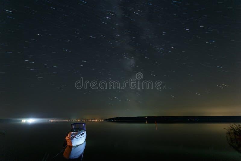 Ландшафт ночи озера с причаленными шлюпкой и небом с следами звезды стоковое изображение