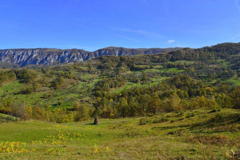 Ландшафт осени с горным селом, стогом сена и горами на расстоянии в Румынии стоковые изображения