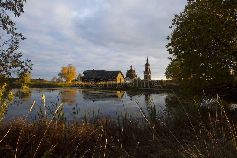 Ландшафт осени с прудом, домом и церковью стоковые изображения