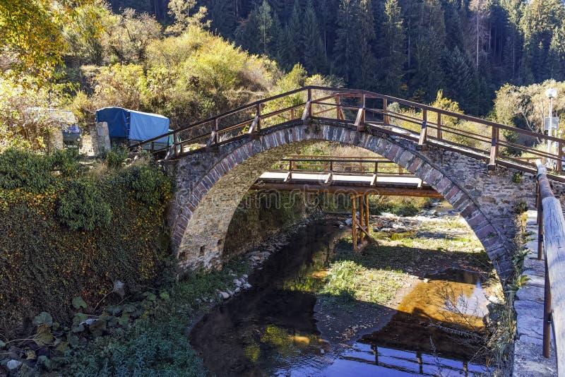 Ландшафт осени с римским мостом и старыми домами в городке Shiroka Laka, Болгарии стоковое фото rf