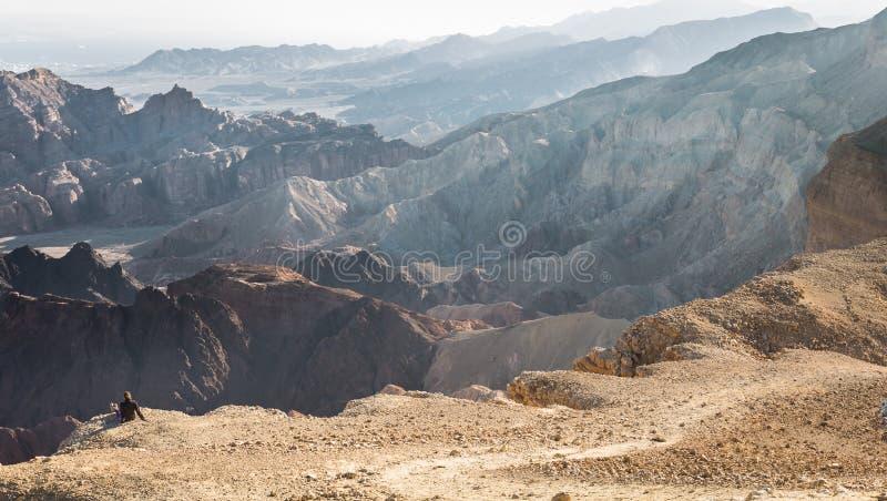 Ландшафт пустыни края горы туриста backpacker женщины сидя отдыхая стоковое изображение
