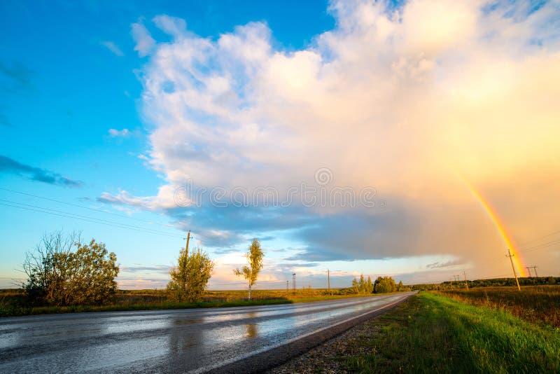 Ландшафт с проселочной дорогой и радугой стоковые фотографии rf