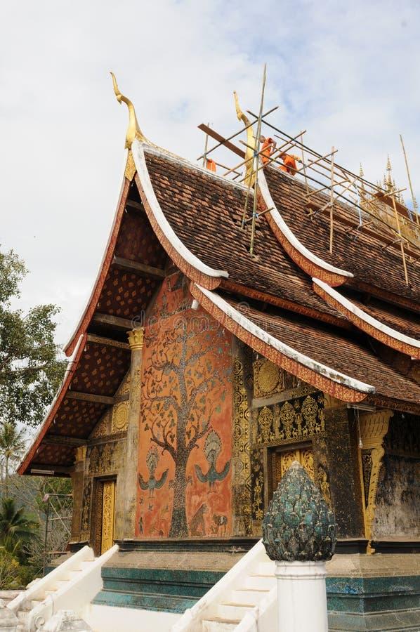 Лаос: монахи делают ремонт крыши на виске ремня Wat Xieng в городе Luang Brabang стоковые изображения rf