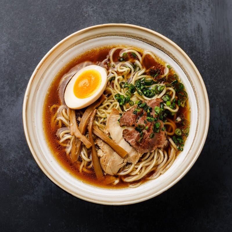 Лапша рамэнов азиатская в отваре с мясом и Ajitama замариновала яйцо в шаре стоковые фото