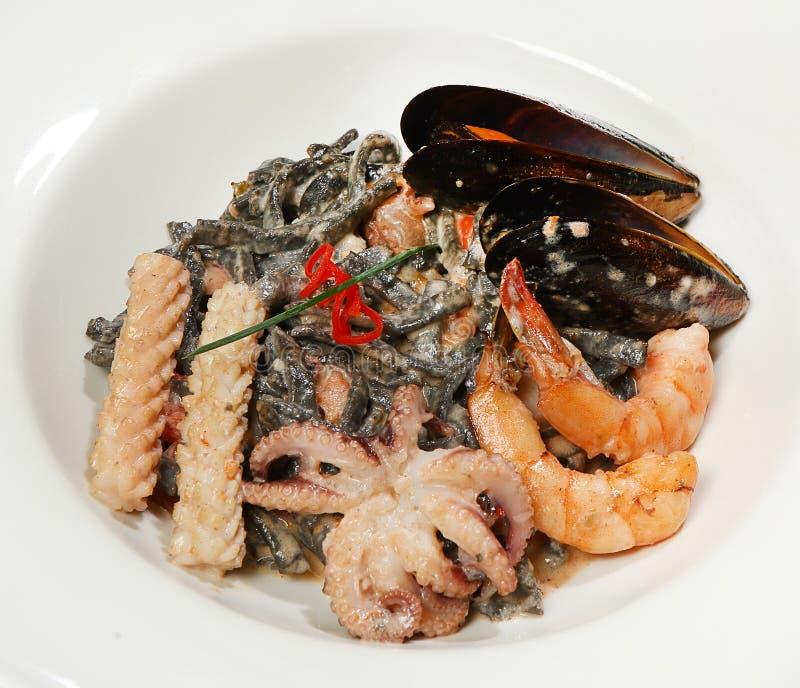 Лапши лапшей стиля вьетнамца первоначально черные с коктеилем моря, мини осьминогами, кальмаром, креветкой и голубыми мидиями в с стоковые изображения rf