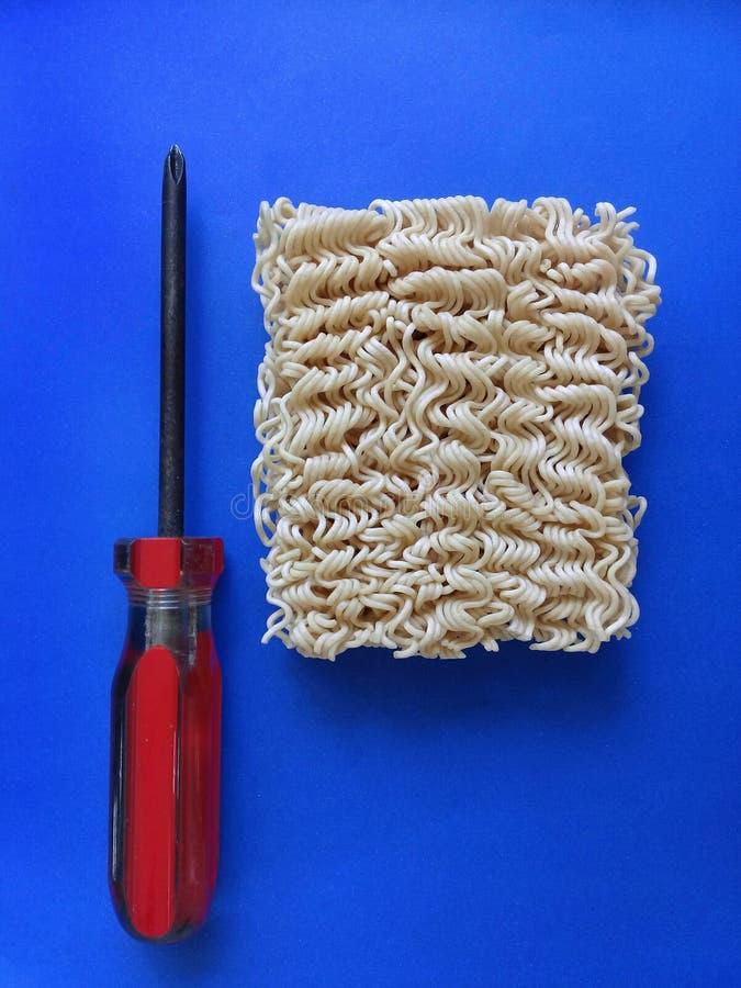 Лапши рамэнов рядом с отверткой - концепция для того чтобы зафиксировать что-нибудь используя лапши - голубая предпосылка стоковое изображение