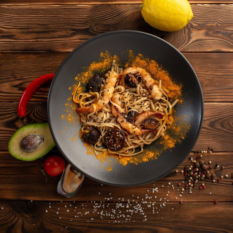 лапши Сингапур-стиля с грибами и креветками шиитаке в плите на деревянной предпосылке стоковое изображение