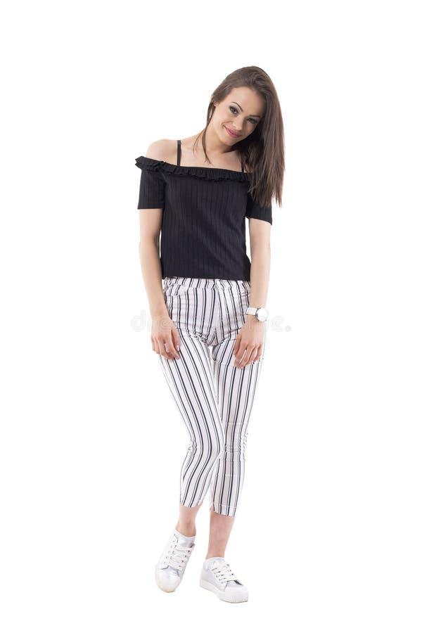 Ласковая застенчивая молодая дама в striped брюках с оружиями вниз усмехаясь и смотря камеру стоковые изображения rf