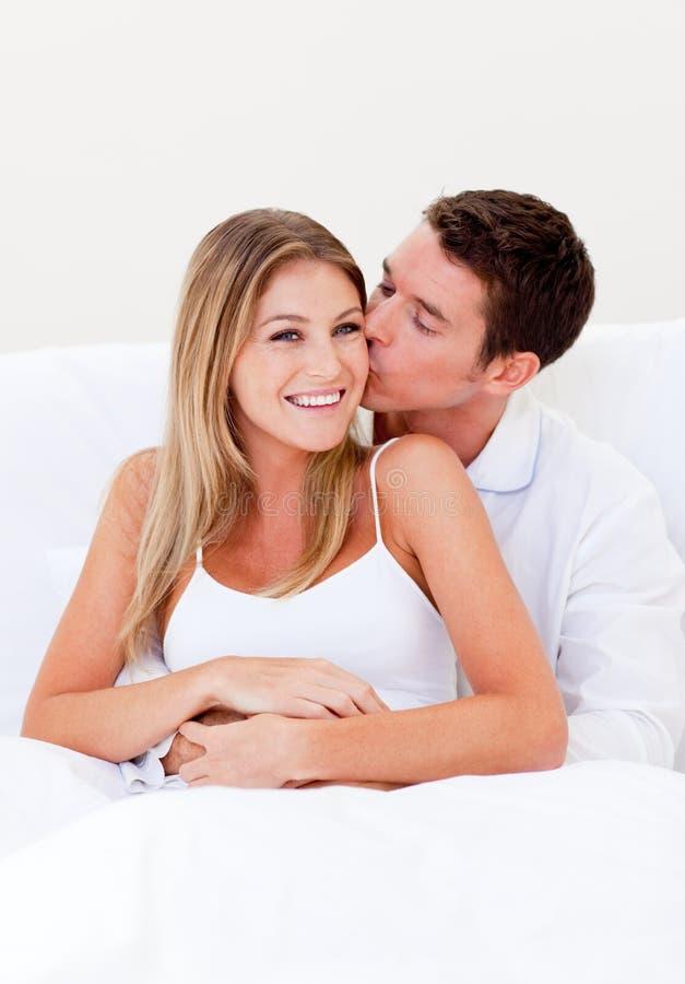 ласковая кровать его целуя супруга человека сидя стоковое изображение rf
