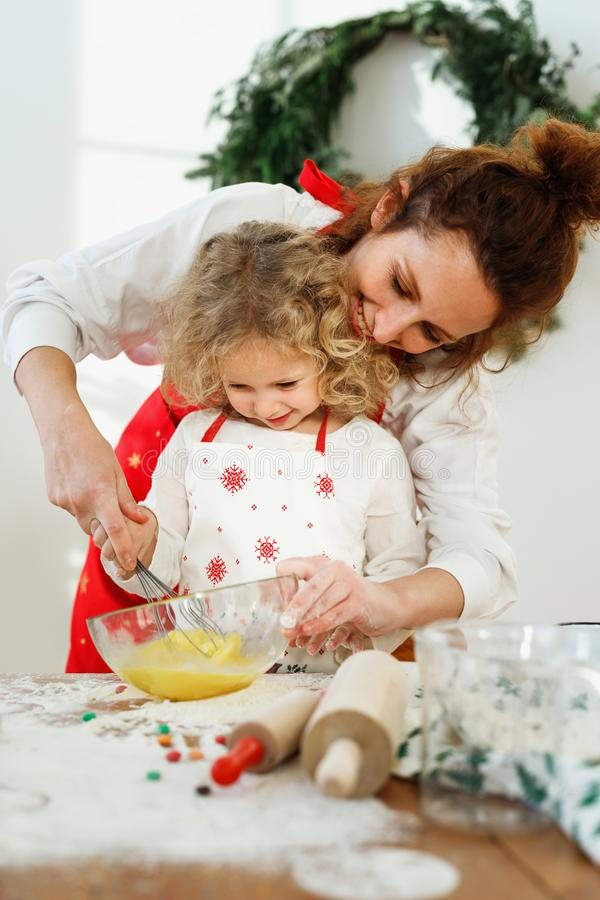 Ласковая мать помогает ее dughter для того чтобы юркнуть яичка в шаре, стоит совместно на кухне, печет очень вкусный пирог для вс стоковое изображение rf