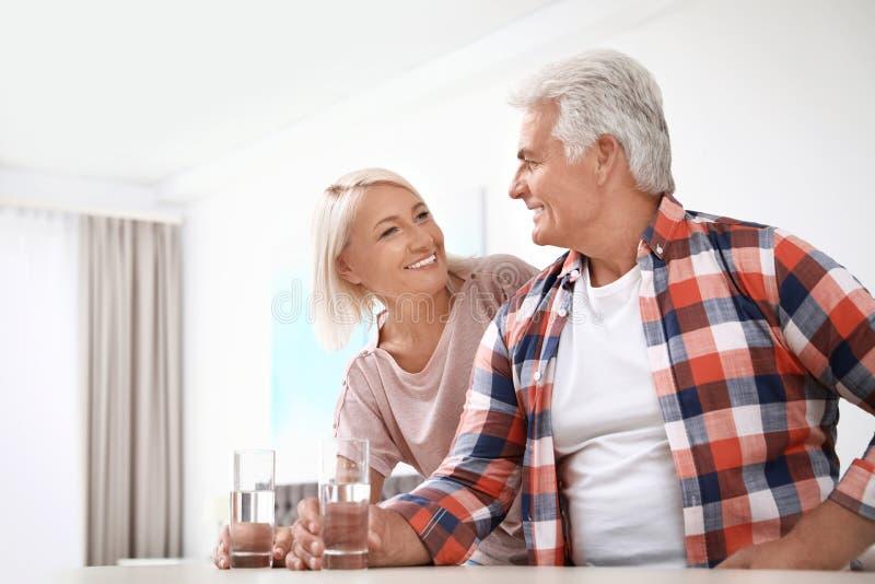 Ласковые старшие пары со стеклами воды дома стоковые фотографии rf