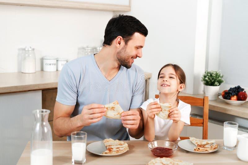 Ласковый приятный смотря отец и его маленькая дочь едят вкусную еду утра на кухне, связывают с каждым стоковые изображения