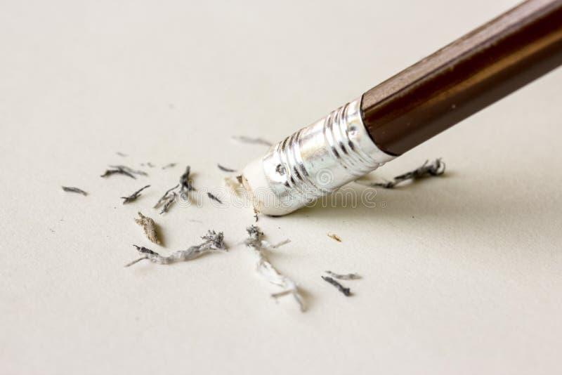 Ластик карандаша извлекая написанную ошибку на куске бумаги стоковое изображение