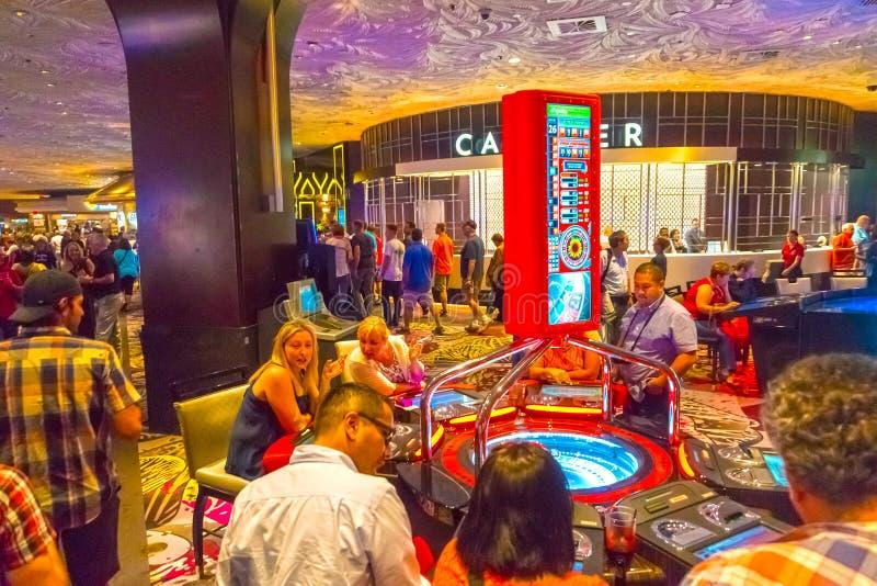 Лас-Вегас, Соединенные Штаты Америки - 6-ое мая 2016: Люди играя на торговых автоматах в гостинице Excalibur и стоковые изображения