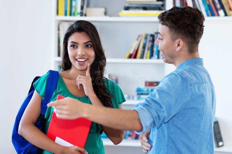 Латино-американская девушка разговаривая с немецким студентом на классе стоковые изображения rf