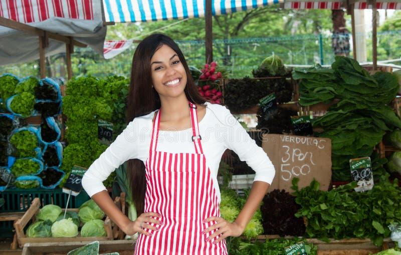 Латино-американская женщина продавая овощи и салат на фермерах mar стоковые изображения rf