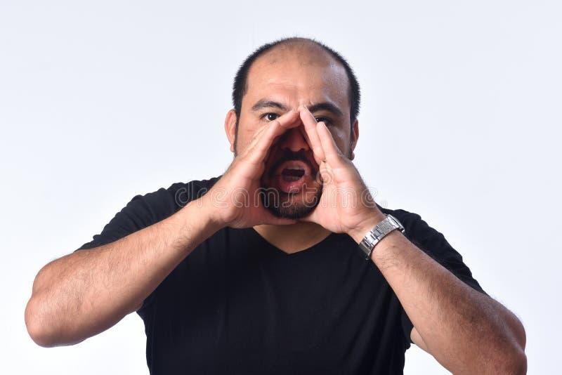 Латино-американский человек кладя руку в рот и кричащ на белой предпосылке стоковая фотография rf