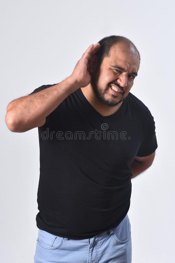 Латино-американский человек кладя руку на ее ухо потому что она не может услышать на белой предпосылке стоковое фото rf