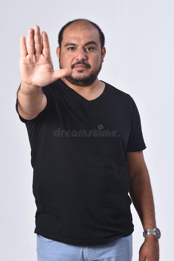 Латино-американский человек с предпосылкой знака стопа белой стоковое изображение rf