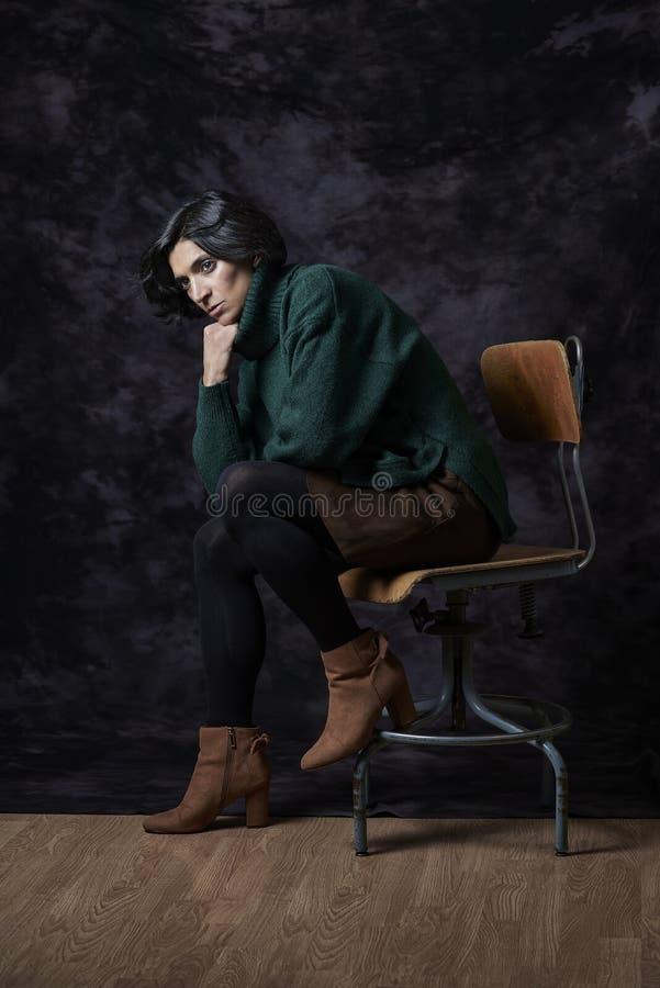 Латинская женщина в обмундировании Осен-зимы сидя перед blac стоковые изображения rf