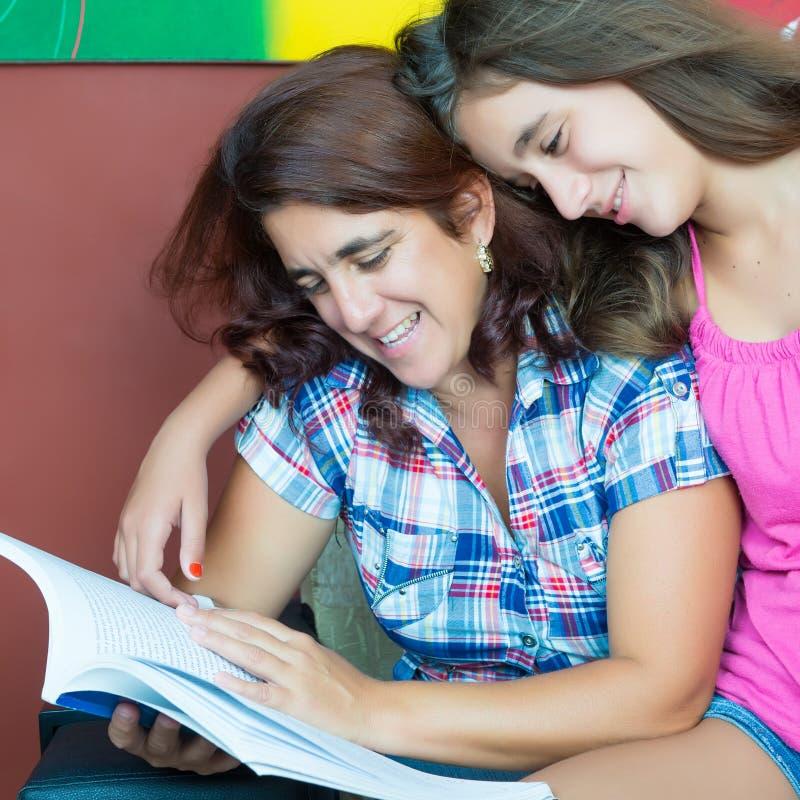 Латинская мать и ее дочь-подросток читая книгу стоковые фото