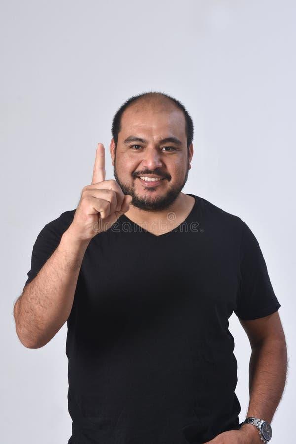 Латинский человек с пальцем в форме номера стоковые фотографии rf