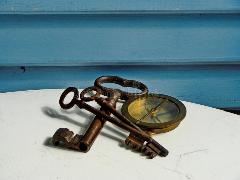Латунный компас военно-морского флота и проутюжить винтажные ключи на белой и голубой предпосылке стоковые фото