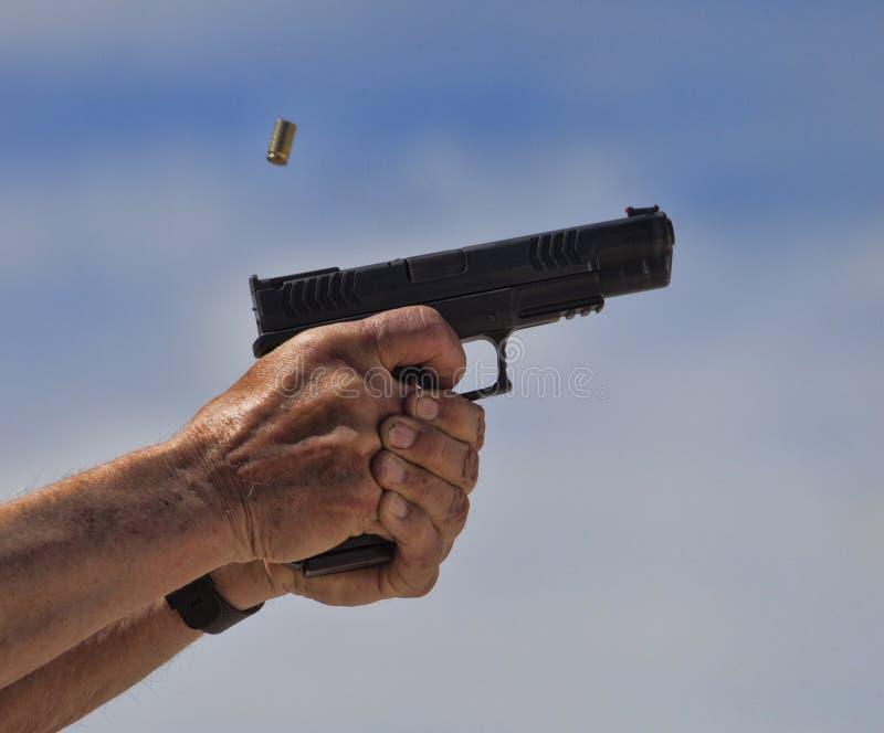Латунь выкидывая от личного огнестрельного оружия которое как раз съемка стоковая фотография