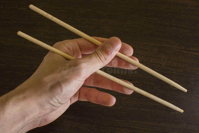 Левая рука человека используя бамбуковые палочки на деревянной предпосылке стоковое фото rf