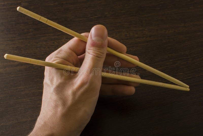 Левая рука человека используя бамбуковые палочки на деревянной предпосылке стоковые фотографии rf