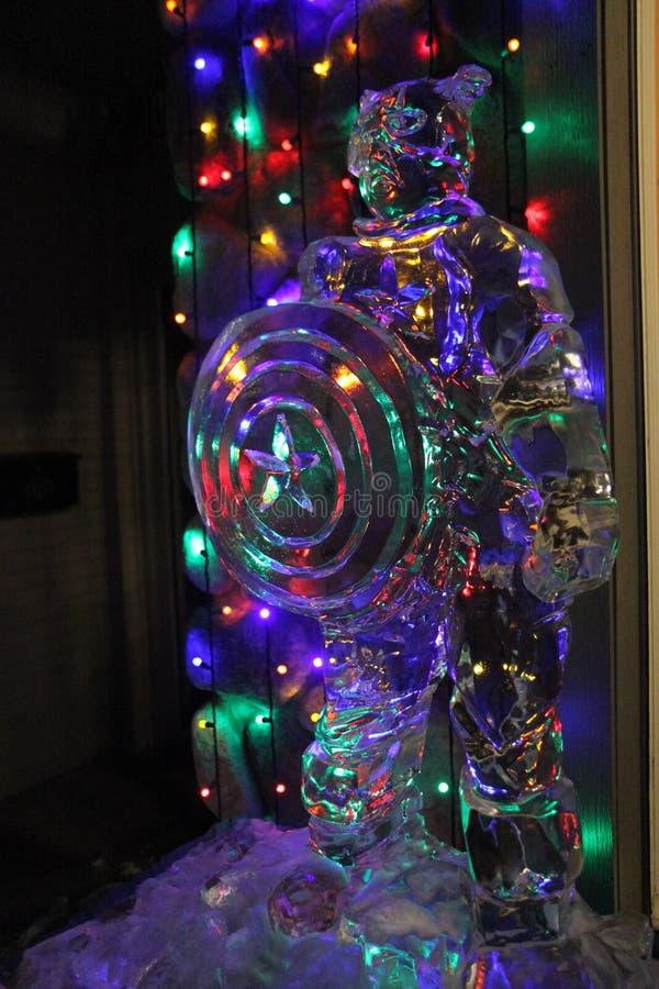 Ледяная скульптура капитана Америки перед светами рождества стоковое фото rf