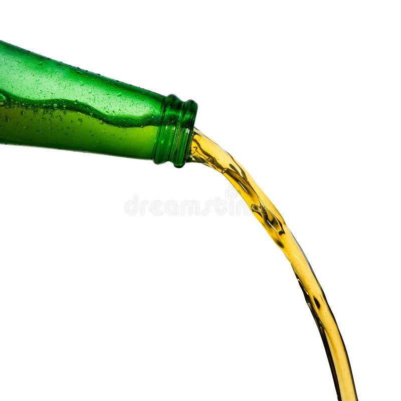 Лед - холодное пиво лить от зеленой бутылки Остановите крупный план действия на белизне стоковые изображения rf
