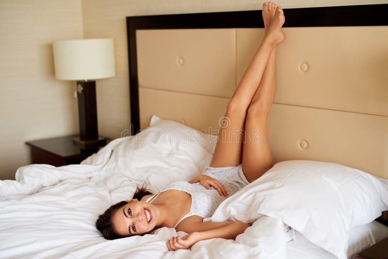 Лежать женщины вверх ногами на кровати усмехаясь на камере стоковые изображения rf