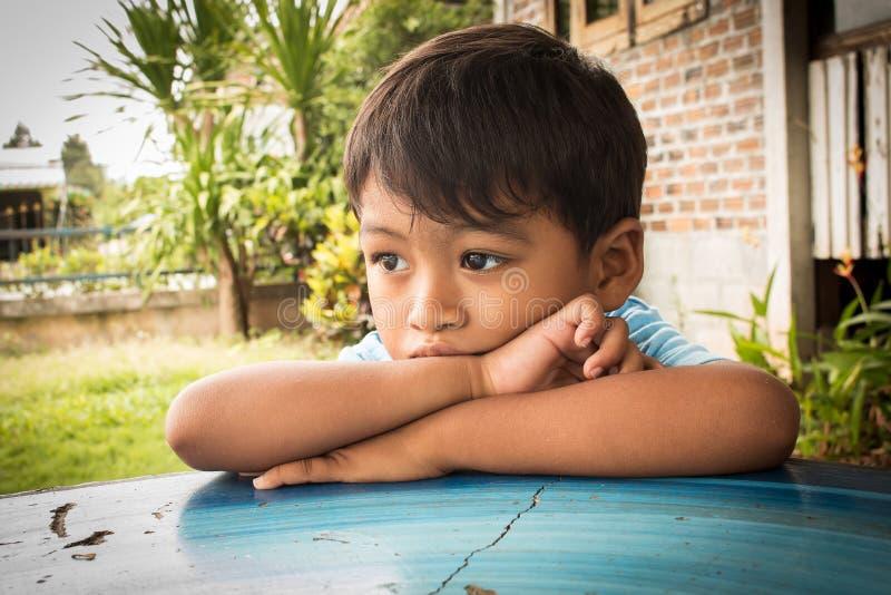 Лежать мальчика унылый и потревоженный на таблице стоковое изображение rf