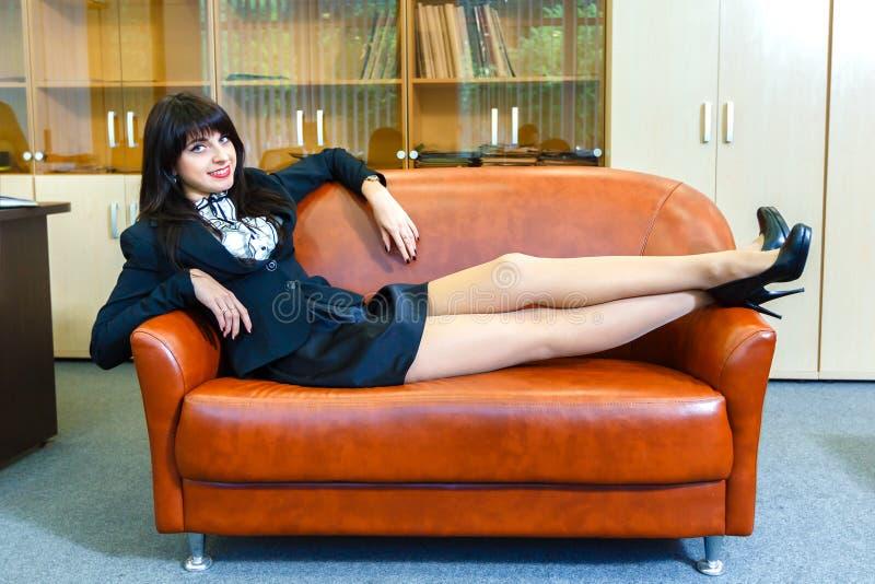 Лежать молодой красивой коммерсантки отдыхая на софе в офисе стоковая фотография