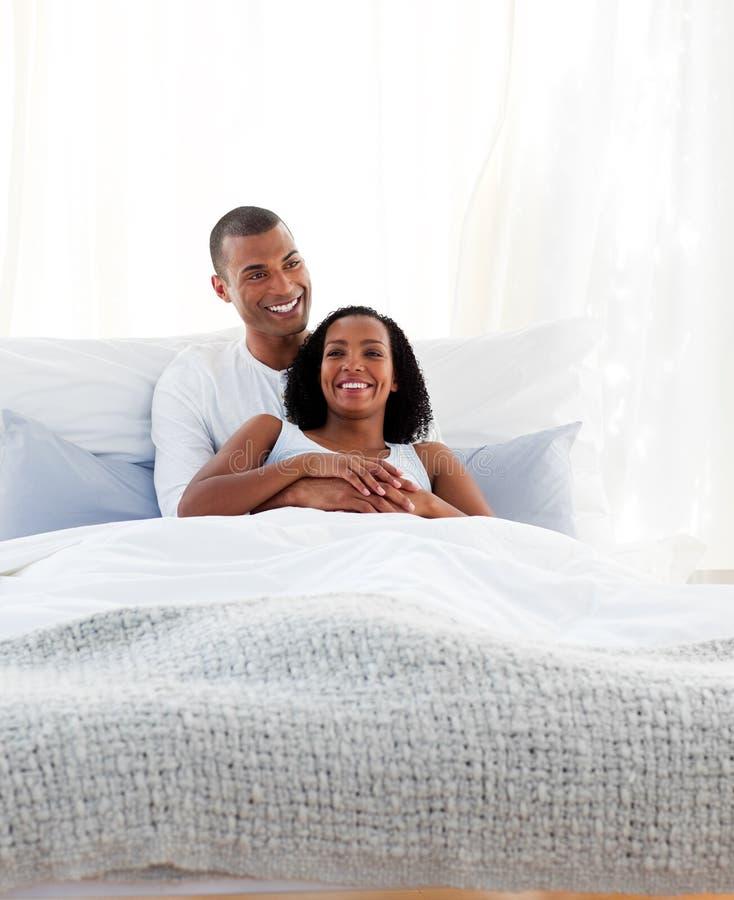 Лежать плотных пар прижимаясь на их кровати стоковая фотография