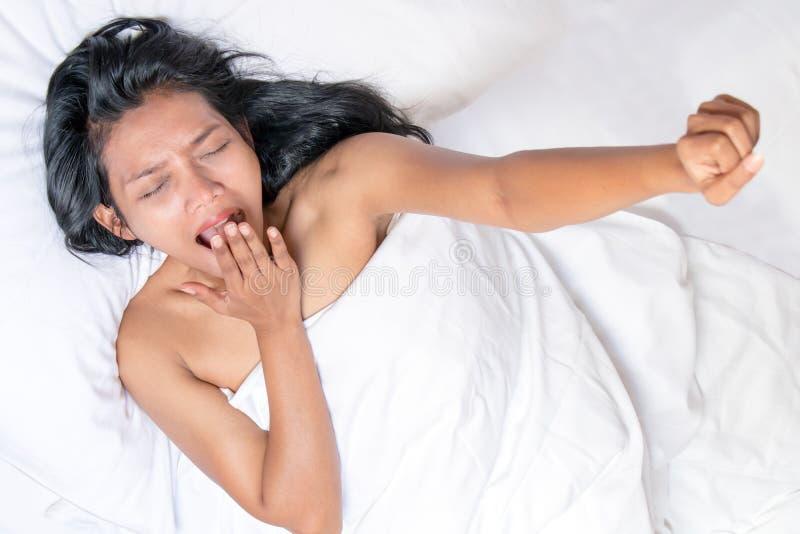 Лежа женщина зевая с рукой вверх стоковое изображение