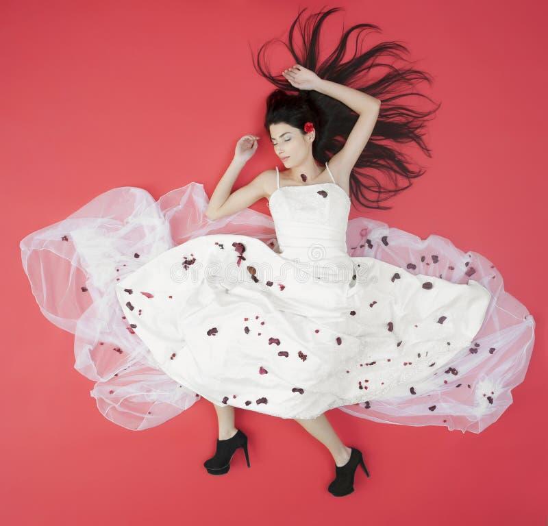 Лежа невеста красоты в белом платье изолированном на красном цвете стоковое изображение