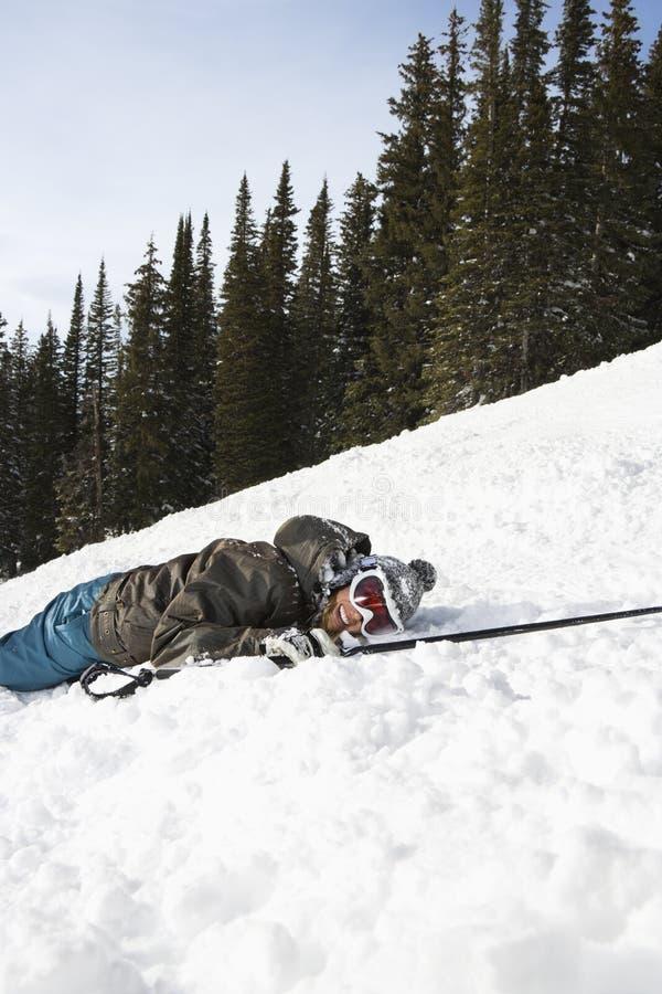 лежа снежок лыжника стоковое фото rf