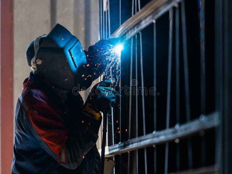 Лейборист промышленного работника на структуре стали дуговой сварки фабрики стоковые фотографии rf