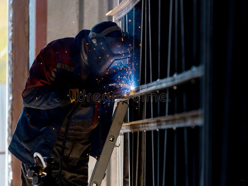 Лейборист промышленного работника на структуре стали дуговой сварки фабрики стоковая фотография