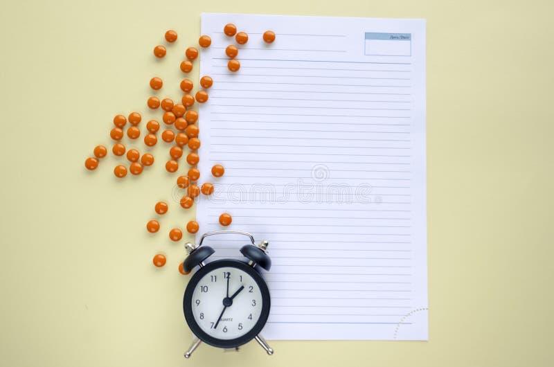 Лекарства и часы рецепта, едят таблетки в срок, пишут вниз на бумаге r стоковые фото