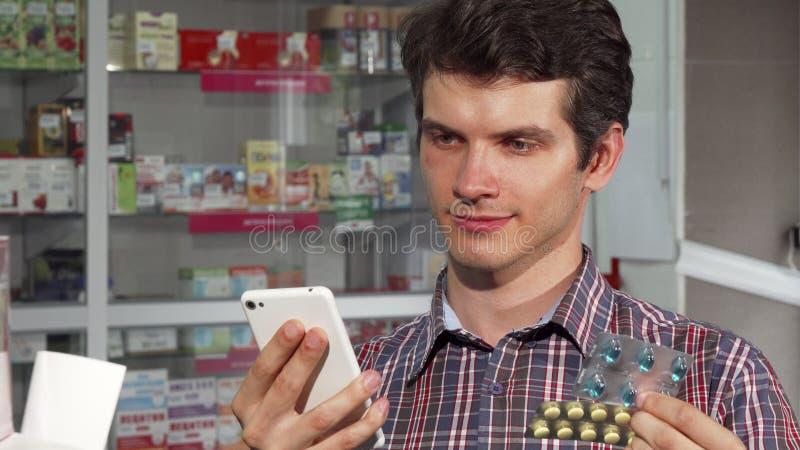 Лекарства молодого человека покупая на аптеке стоковая фотография