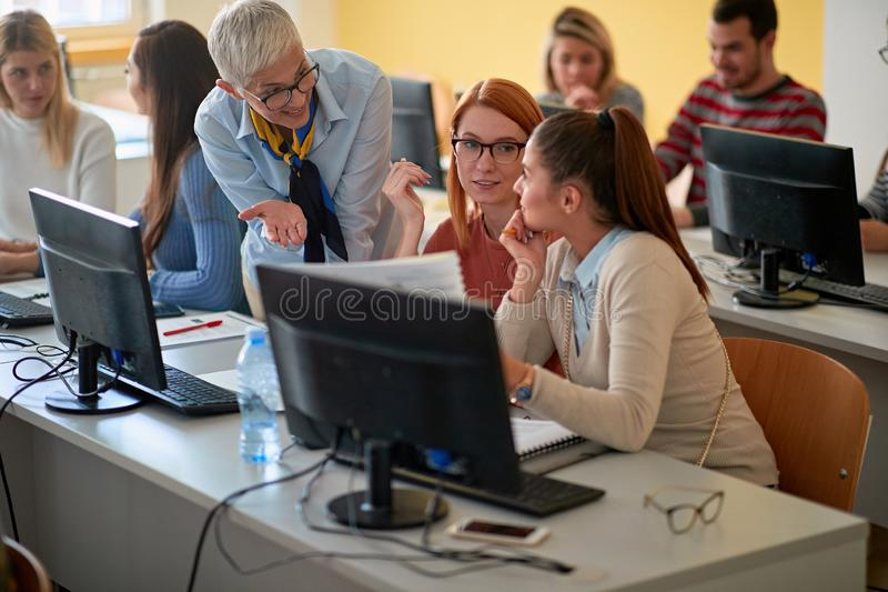Лектор со студентами девушки работая в классе компьютера на университетском кампусе стоковое фото rf