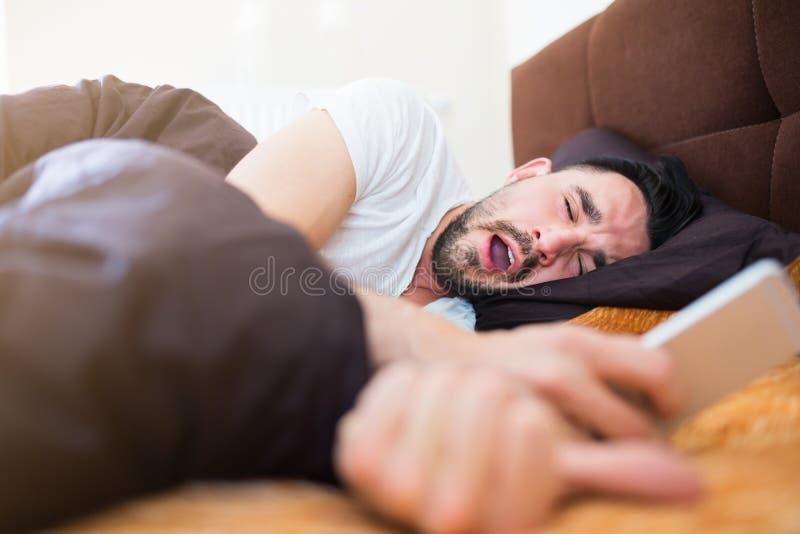 Ленивое утро в кровати с умным телефоном стоковое фото rf